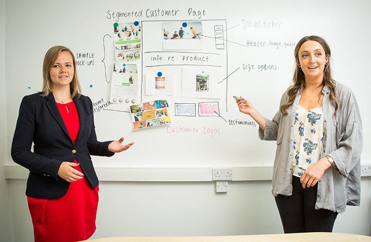 2 women, meeting, white board, brochure, sample